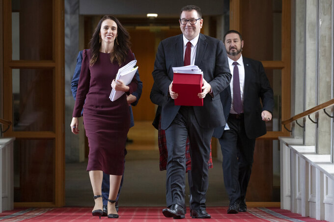 New Zealand Finance Minister Grant Robertson, front right, walks with Prime Minister Jacinda Ardern, left, to deliver his budget to parliament in Wellington, New Zealand, Thursday, May 20, 2021. New Zealand plans to rebuild its Antarctic base and spend billions more on welfare payments as part of a spending program aimed at lifting the economy out of a coronavirus slump. (Mark Mitchell/NZ Herald via AP)