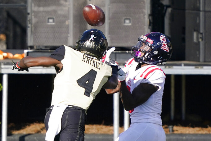 Mississippi wide receiver Elijah Moore, right, catches a touchdown pass as he is defended by Vanderbilt cornerback Randall Haynie (4) in the first half of an NCAA college football game Saturday, Oct. 31, 2020, in Nashville, Tenn. (AP Photo/Mark Humphrey)