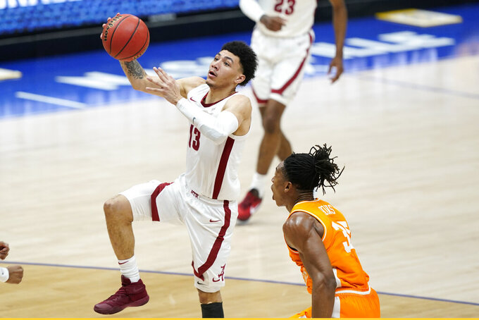 Alabama's Jahvon Quinerly (13) drives past Tennessee's Yves Pons (35) in the first half of an NCAA college basketball game in the Southeastern Conference Tournament Saturday, March 13, 2021, in Nashville, Tenn. (AP Photo/Mark Humphrey)