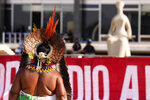 An Indigenous woman walks after the Supreme Court judges' decision to suspend the vote that defines the demarcation of indigenous lands, during a protest in front of the Supreme Court building, in Brasilia, Brazil, Wednesday, Sept. 15, 2021. (AP Photo/Eraldo Peres)