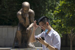A man lowers his mask to smoke as he passes by a statue in the likeness of The Thinker in Beijing, China on Monday, July 6, 2020. (AP Photo/Ng Han Guan)