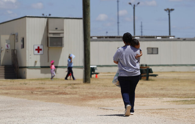 FILE - In this Aug. 23, 2019 file photo, immigrants seeking asylum walk at the ICE South Texas Family Residential Center, in Dilley, Texas. Late Wednesday, Nov. 25, 2020, the U.S. government appealed a judge's order barring the expulsions of immigrant children who crossed the border alone, a policy enacted during the coronavirus pandemic to deny the children asylum protections. (AP Photo/Eric Gay, File)