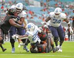 Miami defensive lineman Jonathan Ford (96) fails to stop North Carolina running back Javonte Williams (25) as he scores a touchdown during the first half of an during an NCAA college football game at Hard Rock Stadium In Miami Gardens, Fla, Saturday, Dec, 12, 2020. (Al Diaz/Miami Herald via AP)