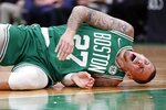Boston Celtics' Daniel Theis lies on the court after being hurt during the first half of the team's NBA basketball game against the Toronto Raptors in Boston, Friday, Oct. 25, 2019. (AP Photo/Michael Dwyer)
