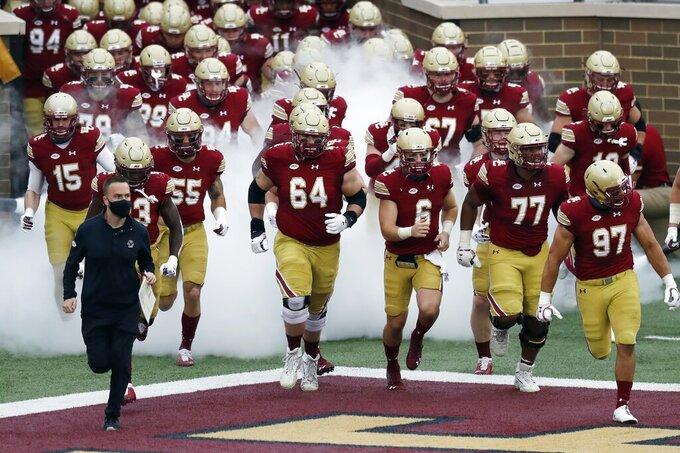 FILE - In this Oct. 24, 2020, file photo, Boston College head coach Jeff Hafley, left, leads his team onto the field before an NCAA college football game against Georgia Tech in Boston. After taking over at Boston College just before the pandemic broke out, Hafley isn't looking for things to get back to normal. (AP Photo/Michael Dwyer, File)