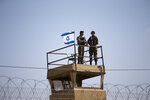 FILE - In this Tuesday, May 15, 2018 file photo, Israeli soldiers guard on top of a watch tower in a community along the Israel- Gaza Strip Border. The modern Middle East has been plagued by ruinous wars: country versus country, civil wars with internecine and sectarian bloodletting, and numerous eruptions centered in the Israeli-Palestinian conflict. But never in the last 70 years have they seemed as interconnected as now with Iran and Saudi Arabia vying for regional control, while Israel also seeks to maintain a military supremacy of its own.(AP Photo/Ariel Schalit, File)