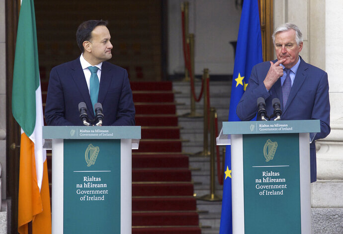 Taoiseach Leo Varadkar, left listens to Michel Barnier, the EU's Brexit negotiator, during a press conference, outside the Government Buildings in Dublin, Monday, Jan. 27, 2020.  Ireland's prime minister has warned Britain that Brexit is far from finished -- and the European Union will have the upper hand in upcoming negotiations on future relations between the two sides. (Damien Eagers/PA via AP)