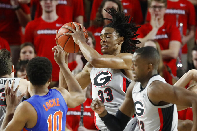 Georgia forward Nicolas Claxton (33) take position of the ball from Florida guard Noah Locke (10) during an NCAA college basketball game in Athens, Ga., on Saturday, Jan. 19, 2019. ( Joshua L. Jones/Athens Banner-Herald via AP)
