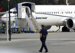 FILE- In this March 14, 2019, file photo a worker walks next to a Boeing 737 MAX 8 airplane parked at Boeing Field in Seattle. U.S. prosecutors are looking into the development of Boeing's 737 Max jets, a person briefed on the matter revealed Monday, the same day French aviation investigators concluded there were