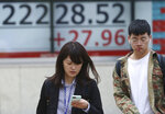 People walk by an electronic stock board of a securities firm in Tokyo, Monday, April 22, 2019. Asian stock markets were mixed Monday following the Easter holiday weekend as investors looked ahead to U.S. and Japanese economic data. (AP Photo/Koji Sasahara)