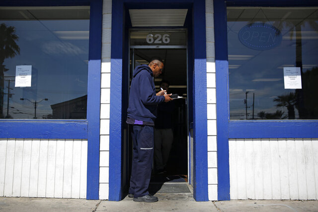 Gyasi Subira, a courier with FedEx, delivers a package at a business closed to the public along his route amid the coronavirus outbreak Friday, March 27, 2020, in Las Vegas. The new coronavirus causes mild or moderate symptoms for most people, but for some, especially older adults and people with existing health problems, it can cause more severe illness or death. (AP Photo/John Locher)