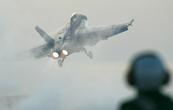 FILE - In this April 11, 2003 file photo, a flight deck handler watches as an F/A 18E Super Hornet is launched from the USS Nimitz in the Prsian Gulf. The Navy says a fighter jet has crashed in the Mojave Desert but its pilot safely ejected. The F/A-18E Super Hornet from Naval Air Station Lemoore in California's Central Valley went down Tuesday, Oct. 20, 2020 in Superior Valley south of Naval Air Weapons Station China Lake. (AP Photo/Richard Vogel, File)