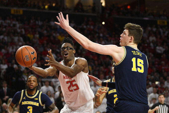 Maryland forward Jalen Smith (25) and Michigan center Jon Teske (15) battle for the ball during the second half of an NCAA college basketball game, Sunday, March 8, 2020, in College Park, Md. (AP Photo/Nick Wass)