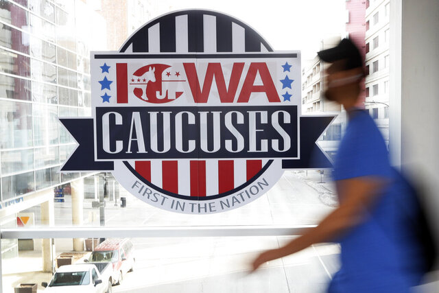 File-In this Feb. 4, 2020, file photo, a pedestrian walks past a sign for the Iowa Caucuses on a downtown skywalk, in Des Moines, Iowa. The Iowa Democratic Party is agreeing to recount the results in about two dozen of almost 1,700 precinct caucuses as part of the ongoing process to resolve the weeks-long question of who won Iowa's tarnished presidential caucuses. Campaign officials for former South Bend Mayor Pete Buttigieg and Vermont Sen. Bernie Sanders asked for a combined 23 precincts to be recounted. (AP Photo/Charlie Neibergall, File)