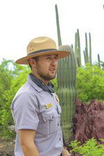"""Park Ranger Freddy Fernandez-Ramirez describes the washes in Saguaro National Park Ariz., as the """"desert's highway."""" He spends a lot of time exploring these areas in the Tucson park. The 30-year-old was recruited eight years ago as part of an effort to get younger generations involved in national parks. (Sofia Krusmark/The Arizona Republic via AP)"""