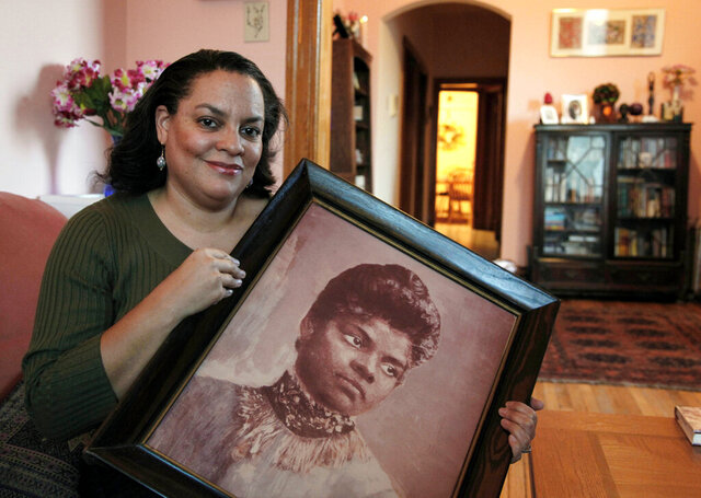 "FILE - In this Dec. 2, 2011 file photo, Michelle Duster, great-granddaughter of civil rights pioneer Ida B. Wells who led a crusade against lynching during the early 20th century, holds a portrait of Wells in her home in Chicago's South Side. Duster's biography of the pioneering African-American journalist and activist, ""Ida B. the Queen"" will come out next February.  (AP Photo/Charles Rex Arbogast, File)"