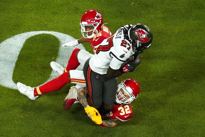 Tampa Bay Buccaneers running back Ronald Jones (27) is tackled by Kansas City Chiefs' Tyrann Mathieu (32) and Charvarius Ward (35) during the first half of the NFL Super Bowl 55 football game Sunday, Feb. 7, 2021, in Tampa, Fla. (AP Photo/Charlie Riedel)