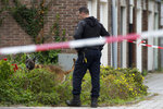 A forensics expert with his dog search for evidence in the area where a lawyer who represented a key witness in a major Dutch organized crime trial was gunned down in Amsterdam, in Amsterdam, Netherlands, Wednesday, Sept. 18, 2019. Police said that 44-year-old lawyer Derk Wiersum was fatally shot Tuesday morning by a man who fled on foot and was still being hunted. (AP Photo/Peter Dejong)