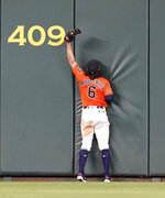 Houston Astros center fielder Jake Marisnick hits the wall after catching a fly ball by Boston Red Sox's Andrew Benintendi during the ninth inning of a baseball game Friday, May 24, 2019, in Houston. The Astros won 4-3. (AP Photo/David J. Phillip)
