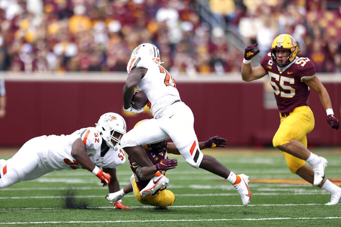 Bowling Green safety Davion Daniels (26) avoids a tackle by Minnesota defensive back Coney Durr (16) during an NCAA college football game Saturday, Sept. 25, 2021, in Minneapolis. (AP Photo/Stacy Bengs)