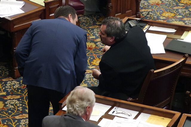 Kansas state Sen. Dennis Pyle, left, R-Hiawatha, confers with Sen. Richard Hilderbrand, R-Galena, while senators debate a sweeping coronavirus measure, early Friday, May 22, 2020, at the Statehouse in Topeka, Kan. Republicans pushed the bill to passage, and it curbs Democratic Gov. Laura Kelly's power to direct the state's pandemic response. (AP Photo/John Hanna)