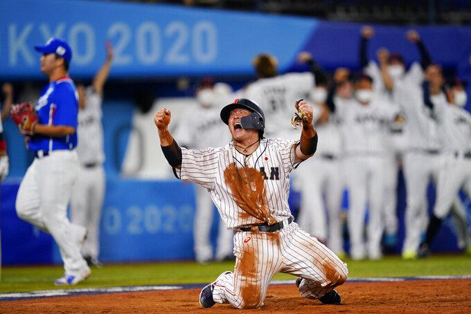 Japan's Takuya Kai reacts after scoring on a three run double by Tetsuto Yamada in the eight inning of a semi-final baseball game against South Korea at the 2020 Summer Olympics, Wednesday, Aug. 4, 2021, in Yokohama, Japan. (AP Photo/Matt Slocum)