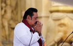Sri Lanka's former President Mahinda Rajapaksa, prays before being sworn in as the prime minister at Kelaniya Royal Buddhist temple in Colombo, Sri Lanka, Sunday, Aug. 9, 2020. (AP Photo/Eranga Jayawardena)