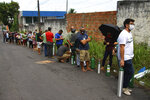 Family members of patients hospitalized with COVID-19 line up with empty oxygen tanks in an attempt to refill them, outside the Nitron da Amazonia company, in Manaus, Amazonas state, Brazil, Friday, Jan. 15, 2021. (AP Photo/Edmar Barros)