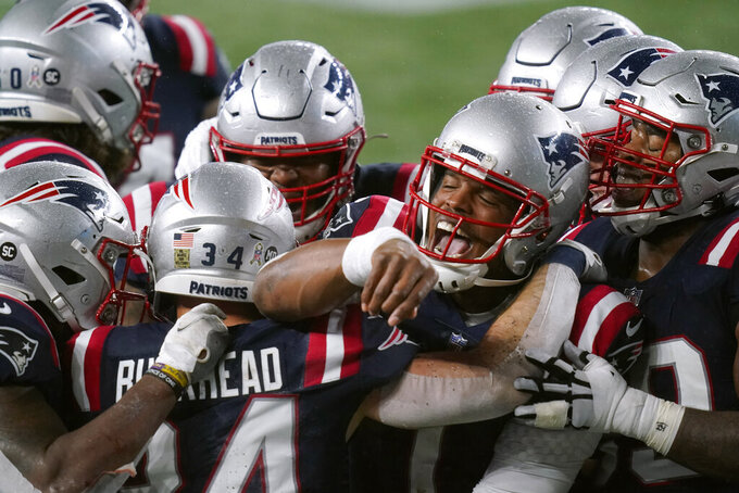 New England Patriots quarterback Cam Newton, right, celebrates with teammates after running back Rex Burkhead, left, caught a touchdown pass thrown by wide receiver Jakobi Meyers in the first half of an NFL football game against the Baltimore Ravens, Sunday, Nov. 15, 2020, in Foxborough, Mass. (AP Photo/Elise Amendola)