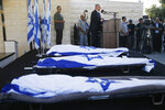"""FILE - In this July 1, 2014 file photo, Israeli Prime Minister Benjamin Netanyahu eulogizes three Israeli teens who were abducted and killed in the West Bank during their joint funeral in the Israeli city of Modiin. HBO's new docudrama series about the killings of four Israeli and Palestinian teenagers, which set off a cascade of events leading to the 2014 Gaza war, is set to air next week and is likely to reopen wounds on both sides of the conflict. """"Our Boys,"""" co-created by Palestinian and Israeli filmmakers, presents a dramatized rendition of the chaotic events of that June following the abduction of three Israeli teens in the West Bank. (AP Photo/Baz Ratner, Pool, File)"""