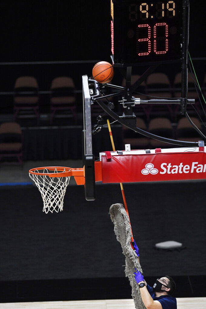 A staff member working in Bubbleville uses a mop to dislodge a stuck basketball ball during the first half of an NCAA college basketball game between UMass-Lowell and North Carolina State, Thursday, Dec. 3, 2020, in Uncasville, Conn. (AP Photo/Jessica Hill)