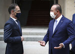 FILE - In this Thursday, July 2, 2020 file photo, Turkey's Foreign Minister Mevlut Cavusoglu, right, and Germany''s Foreign Minister Heiko Maas, wearing face masks to protect against the spread of coronavirus, speak after a meeting in Berlin. A festering row between France and Turkey over a naval standoff in the Mediterranean Sea has shone a glaring searchlight on NATO's struggle to keep order among its ranks and exposed weaknesses in a military alliance that can only take action by consensus. (Cem Ozdel/Turkish Foreign Ministry via AP, Pool, File)