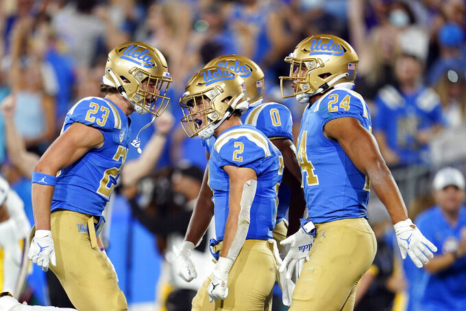 UCLA wide receiver Kyle Philips (2) celebrates his touchdown reception with teammates during the second half of an NCAA college football game against LSU on Saturday, Sept. 4, 2021, in Pasadena, Calif. (AP Photo/Marcio Jose Sanchez)