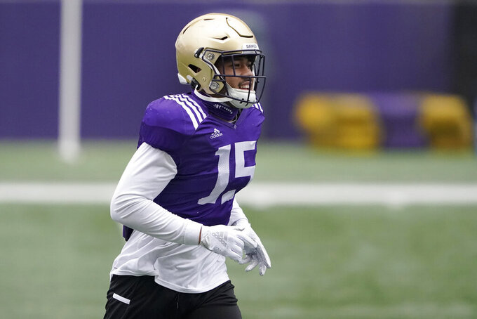 Washington linebacker Daniel Heimuli runs on the field at the start of NCAA college football practice, Friday, Oct. 16, 2020, in Seattle. (AP Photo/Ted S. Warren)