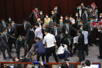 Pro-establishment politician, Starry Lee, center, speaks as pan-democratic legislators scuffle with security guards and pro-China legislators during a Legislative Council's House Committee meeting, in Hong Kong, Friday, May 8, 2020. Scuffles also broke out when Lee called the meeting to order, with pro-democracy lawmakers rushing the table as security shoved back. Security guards physically carried out pro-democracy lawmakers Chu Hoi Dick and Ray Chan, who were ordered to leave due to disorderly conduct. (AP Photo/Kin Cheung)