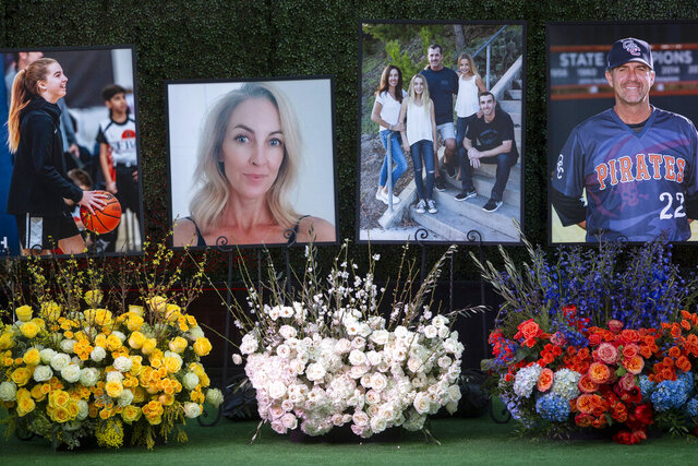 FILE - In this Feb. 10, 2020 file photo, flowers and photos honor members of the Altobelli family outside Angel Stadium in Anaheim, Calif. Coach John Altobelli, 56, far right, his wife, Keri, 43, second from left, and his daughter Alyssa, 13, left, died in a helicopter crash on Jan. 26 in Calabasas. Family members of four of the people killed in a helicopter crash with Bryant and his daughter are suing the companies that owned and operated the aircraft. The wrongful death lawsuits were filed electronically Sunday, April 19, 2020 in Los Angeles Superior Court on behalf of three members of one family and a woman who helped coach Bryant's daughter in basketball. One suit was filed by two children of Orange Coast College baseball coach John Altobelli,his wife and daughter, who played basketball with Gianna. Another suit was filed by the husband and three children of Christina Mauser, who helped Bryant coach the girls' basketball team. (AP Photo/Damian Dovarganes, File)
