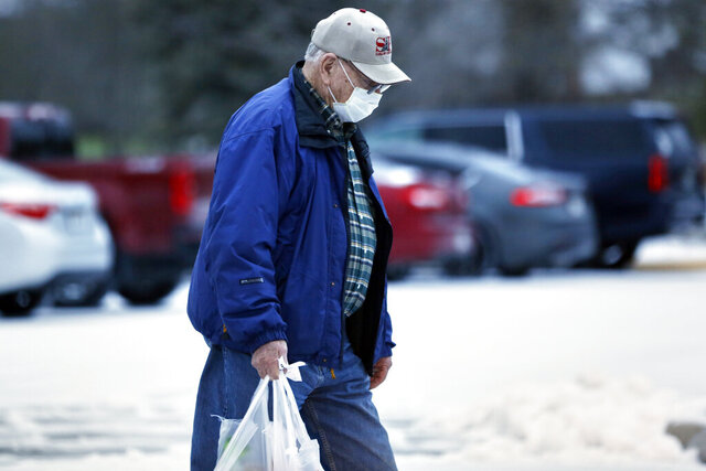 A shopper carries his groceries outside a Hy-Vee supermarket in Omaha, Neb., early Friday, April 3, 2020, during the hour of shopping reserved for those considered at a higher risk of contracting the coronavirus. (AP Photo/Nati Harnik)
