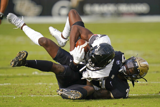Central Florida defensive back Richie Grant, right, tackles Cincinnati wide receiver Jayshon Jackson after a reception during the first half of an NCAA college football game, Saturday, Nov. 21, 2020, in Orlando, Fla. (AP Photo/John Raoux)