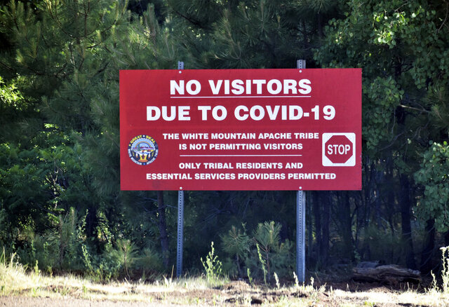 In this Thursday, June 25, 2020 photo provided by C.M. Clay, a sign alerts motorists that visitors are not allowed on the Fort Apache Indian Reservation in eastern Arizona. The reservation, home to the White Mountain Apache Tribe, will be under lockdown this weekend to help slow the spread of the coronavirus. (C.M. Clay/White Mountain Apache Tribe via AP)