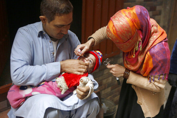 A healthcare worker administers a polio vaccine to a child in Lahore, Pakistan, Monday, Jan. 11, 2021. Despite a steady rise in coronavirus cases, Pakistan on Monday launched a five-day vaccination campaign against polio amid tight security, hoping to eradicate the crippling children's disease this year. (AP Photo/K.M. Chaudary)