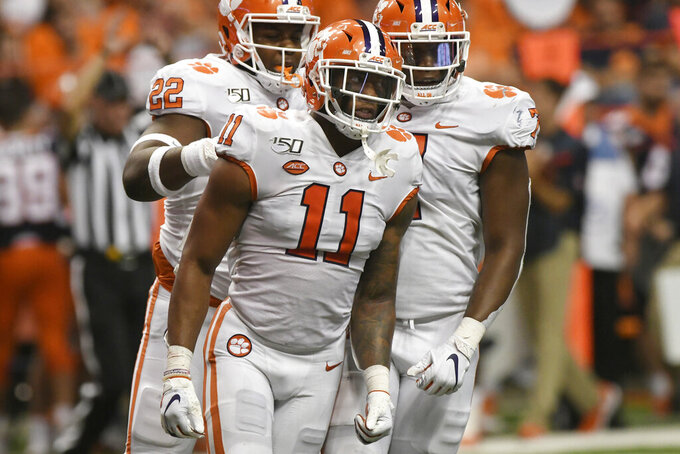 FILE - In this Sept. 14, 2019, file photo, Clemson's Isaiah Simmons celebrates a sack against Syracuse during an NCAA college football game in Syracuse, N.Y. Detroit Lions general manager Bob Quinn sounds very interested in Simmons, adding NFL teams will have a lot of conversations internally about whether he projects to be a linebacker, a safety or a hybrid. (AP Photo/Steve Jacobs, File)
