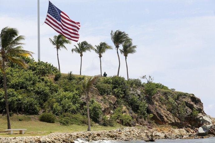 """A man stands near a U.S. flag at half staff on Little St. James Island, in the U. S. Virgin Islands, a property owned by Jeffrey Epstein, Wednesday, Aug. 14, 2019. Tourists and locals alike are powering up boats to take a closer look at a place nicknamed """"Pedophile Island' that lies just off the southeast coast of St. Thomas. (AP Photo/Gabriel Lopez Albarran)"""