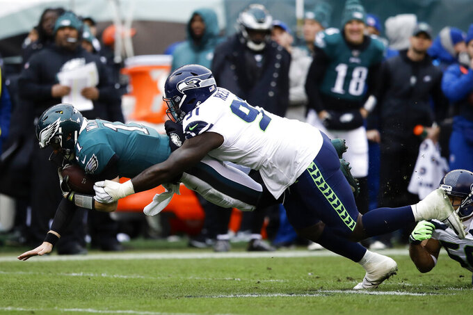 Philadelphia Eagles' Carson Wentz (11) dives against Seattle Seahawks' Jarran Reed (91) during the first half of an NFL football game, Sunday, Nov. 24, 2019, in Philadelphia. (AP Photo/Matt Rourke)