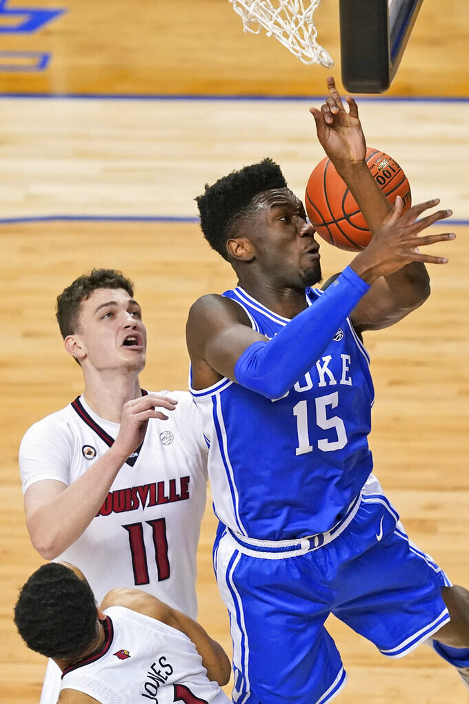 Duke center Mark Williams (15) misses a shot as Louisville forward Quinn Slazinski (11) defends during the first half of an NCAA college basketball game in the second round of the Atlantic Coast Conference tournament in Greensboro, N.C., Wednesday, March 10, 2021. (AP Photo/Gerry Broome)
