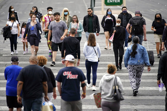 Masked and unmasked pedestrians walk along the Las Vegas Strip, Tuesday, April 27, 2021, in Las Vegas. The Centers for Disease Control and Prevention eased its guidelines Tuesday on the wearing of masks outdoors, saying fully vaccinated Americans don't need to cover their faces anymore unless they are in a big crowd of strangers. (AP Photo/John Locher)