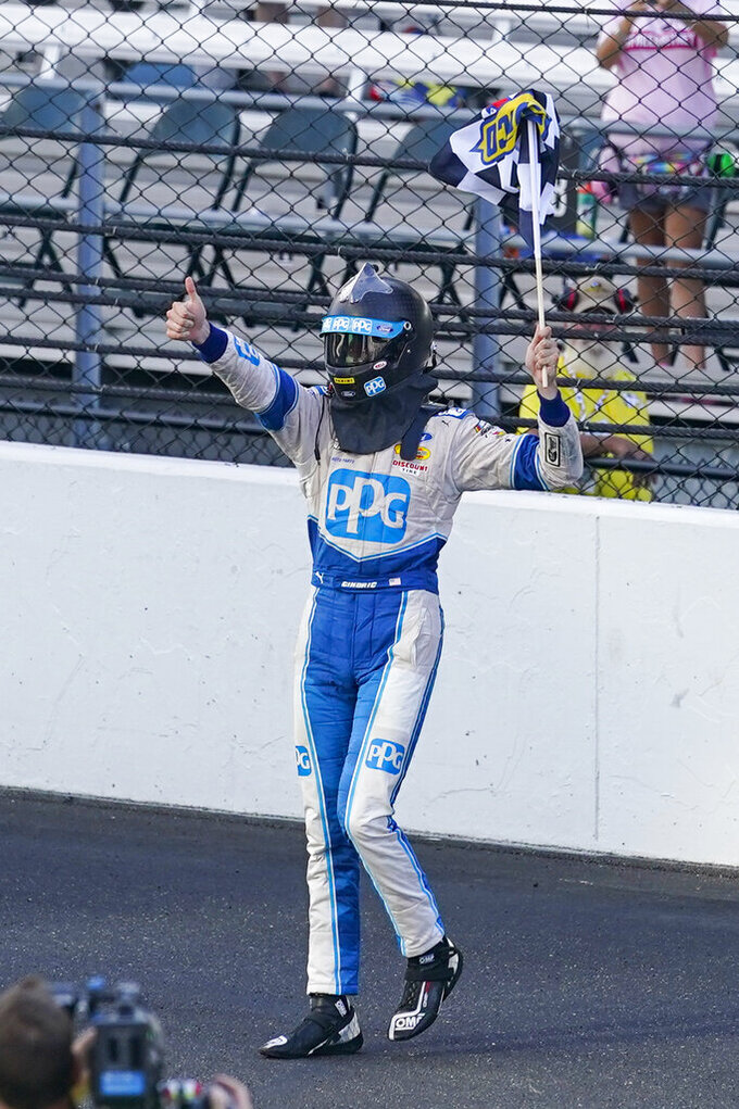 Austin Cindric holds the checkered flag after winning the NASCAR Xfinity Series auto race at Indianapolis Motor Speedway in Indianapolis, Saturday, Aug. 14, 2021. (AP Photo/Darron Cummings)