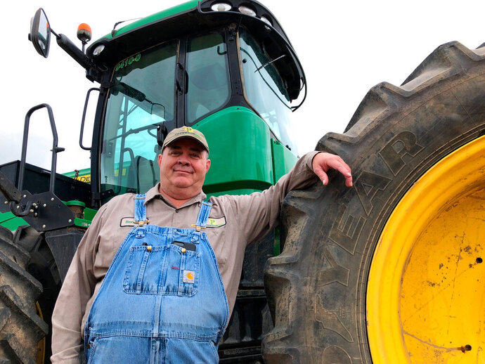 In this Thursday, June 20, 2019, photo, farmer Bernard Peterson leans on a tractor at his farm in Loretto, Ky. When the Trump administration announced a $12 billion aid package for farmers struggling under the financial strain of his trade dispute with China, the payments were capped. But records obtained by The Associated Press under the Freedom of Information Act show that many large farming operations easily found legal ways around the limits to collect big checks. At Peterson's farm, eight members of the family partnership collected a total $863,560 for crops they grow on over 15,000 acres in seven counties, including wheat and corn used at the nearby Maker's Mark bourbon distillery. Peterson said that it didn't make up for all their losses at a time when it was already hard to be profitable. The $1.65 per bushel aid payments for soybeans fell well short of losses he estimated at $2 to $2.50 per bushel, factoring in the loss of the Chinese market that took years to d
