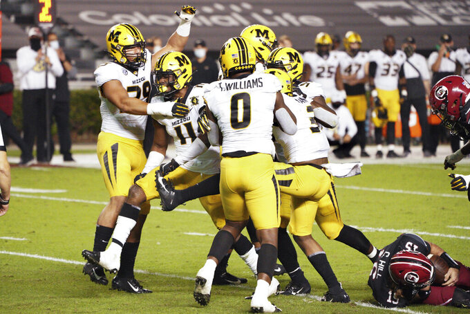 Missouri linebacker Devin Nicholson (11) celebrates a sack with Chris Turner (39), Tre Williams (0) and other teammates during the first half of an NCAA college football game against South Carolina, Saturday, Nov. 21, 2020, in Columbia, S.C. (AP Photo/Sean Rayford)