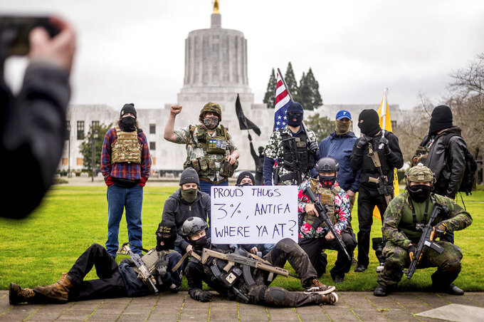 Armed protesters, who identified themselves as Liberty Boys, pose for fellow demonstrators' pictures outside the Oregon State Capitol on Sunday, Jan. 17, 2021, in Salem, Ore. The group said they want reduced government and do not support President Donald Trump or President-elect Joe Biden. (AP Photo/Noah Berger)