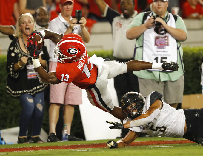 FILE - In this Oct. 6, 2018, file photo, Georgia running back Elijah Holyfield (13) dives into the end zone for a touchdown as Vanderbilt safety LaDarius Wiley (5) defends during the first half of an NCAA college football game, in Atlanta.  Jonathan Ledbetter and Elijah Holyfield say No. 7 Georgia has moved past a lopsided loss at LSU to focus on what's at stake this week. A win over No. 9 Florida would give the Bulldogs the inside track to win the SEC East. Ledbetter and Holyfield sense that  Georgia is rejuvenated after an off week and eager to rejoin the national title race at the annual showdown in Jacksonville. (AP Photo/John Bazemore, File)